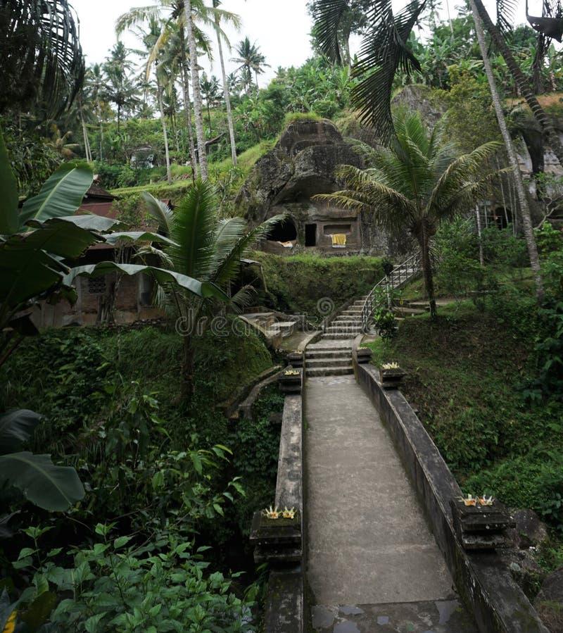 桥梁通过一个石寺庙的巴厘岛印度尼西亚密林 免版税库存照片