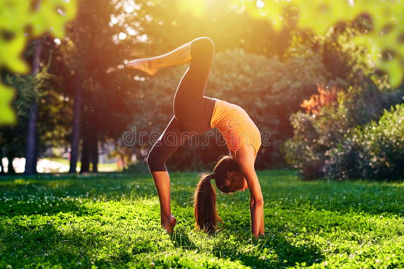 ?? 桥梁锻炼 年轻女人实践的瑜伽或跳舞或者舒展本质上在公园 E 免版税库存照片
