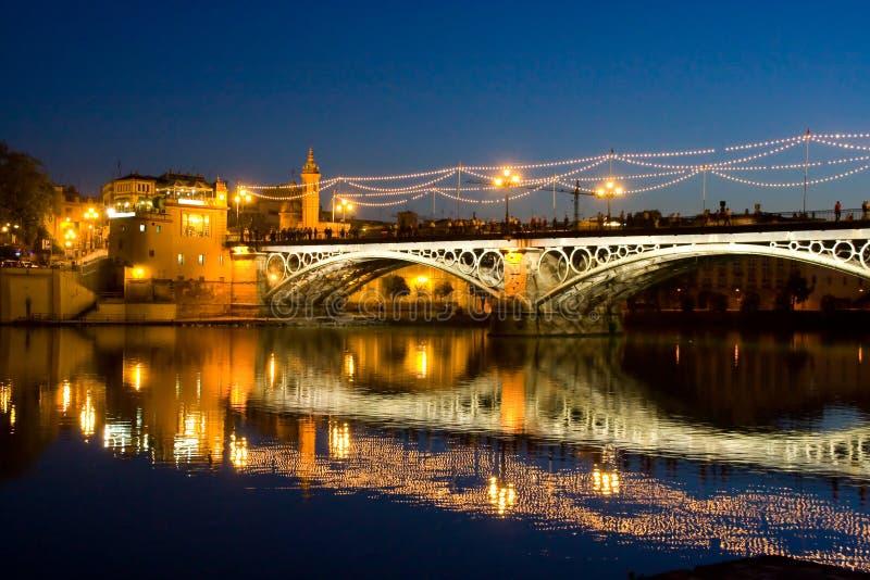 桥梁triana塞维利亚安达卢西亚西班牙在与光的晚上 免版税库存照片