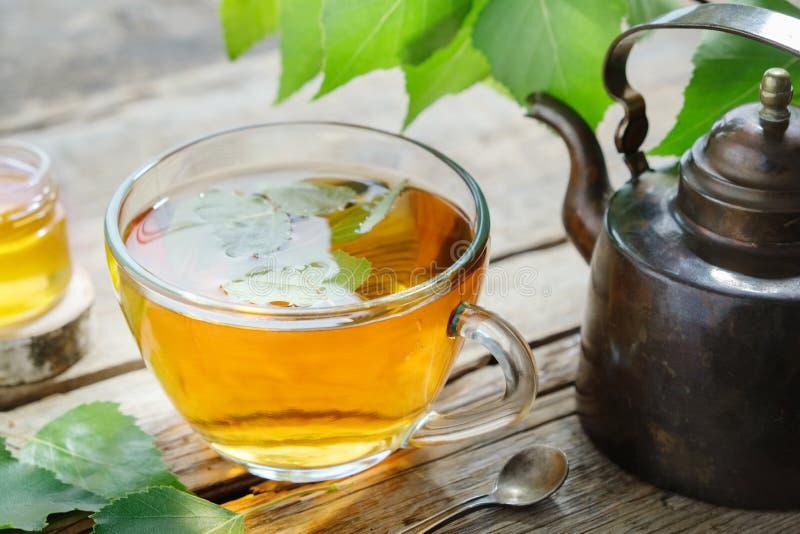 桦树叶子、健康清凉茶杯子、蜂蜜瓶子和葡萄酒铜茶壶 库存图片