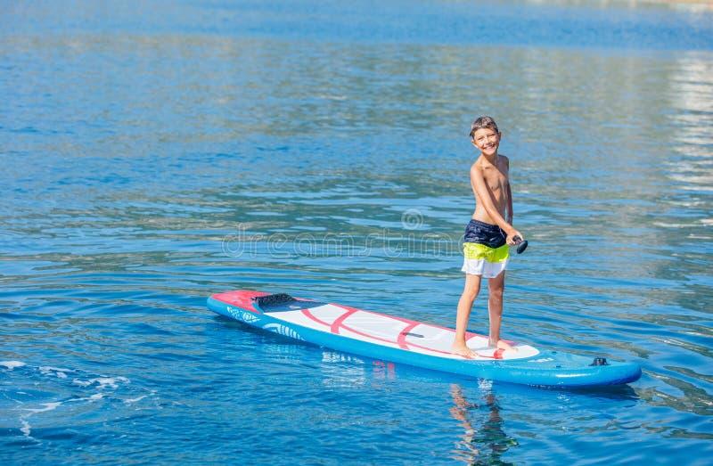 桨房客 用浆划在立场paddleboard的儿童男孩 r 水上运动,一口冲浪的游览 免版税库存图片