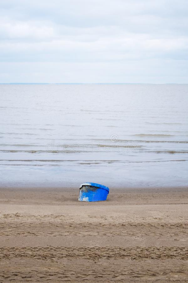 桶与天空和背景的河的看法在海滩的 库存图片