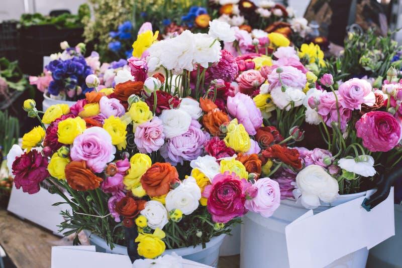 桶充满新鲜的五颜六色的花在农夫市场摊位 图库摄影