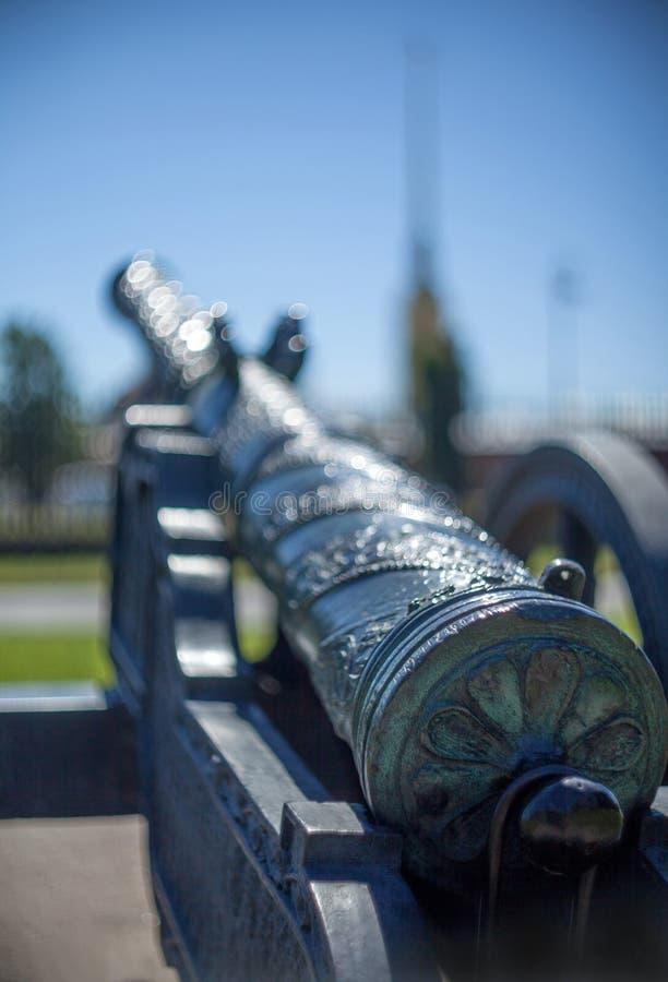 桶在轮子和支架的老葡萄酒生铁大炮有被弄脏的背景 免版税库存图片