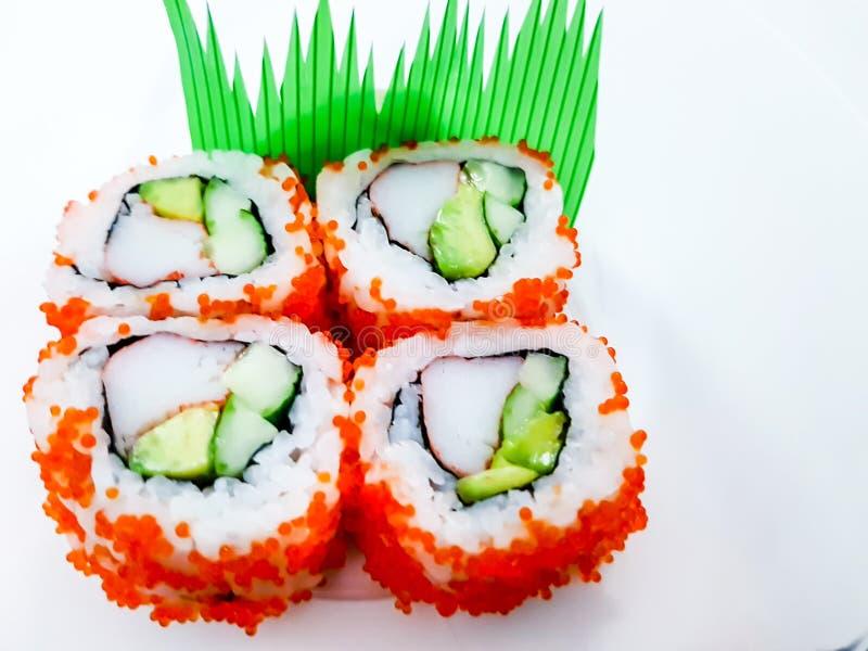 梅基寿司卷、鲕梨和螃蟹寿司简单的白色表面上 图库摄影