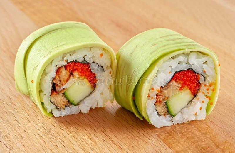 梅基寿司卷用鳗鱼和鲕梨 免版税库存照片
