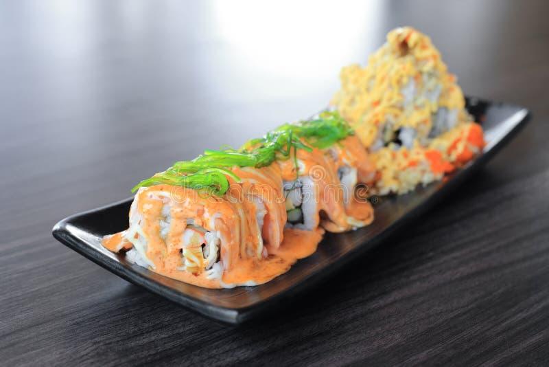 梅基寿司卷由与wakame海草-日本食物的三文鱼上面制成 免版税库存图片