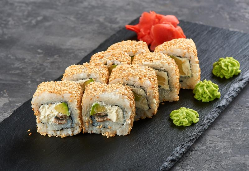 梅基寿司片与三文鱼獐鹿,熏制的鳗鱼,黄瓜,奶油芝士,芝麻,鲕梨的汇集 免版税图库摄影