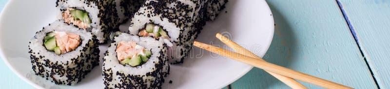 梅基寿司-卷横幅由乳脂干酪、Tamago、黄瓜和熏制的鳗鱼制成里面 外面黑Tobiko 免版税库存照片