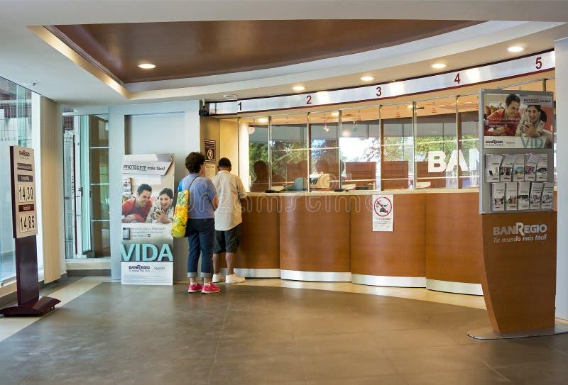 梅里达,尤加坦墨西哥:2015年1月16日:赞助人在一个出纳窗口的改变信仰者货币在墨西哥比索贬值以后 图库摄影