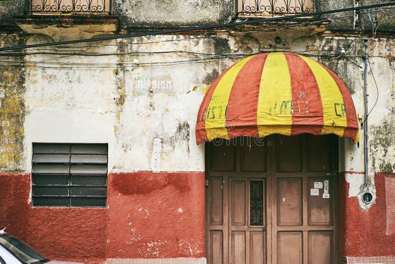 梅里达/尤加坦,墨西哥- 2015年6月1日:有红色和黄色颜色登上的老遮篷在大厦的门在Merdia, Yuc 库存照片