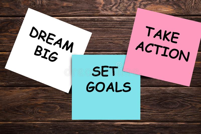 梦想大,集合目标,采取行动概念-诱导忠告或提示在五颜六色的稠粘的笔记关于木桌 库存图片