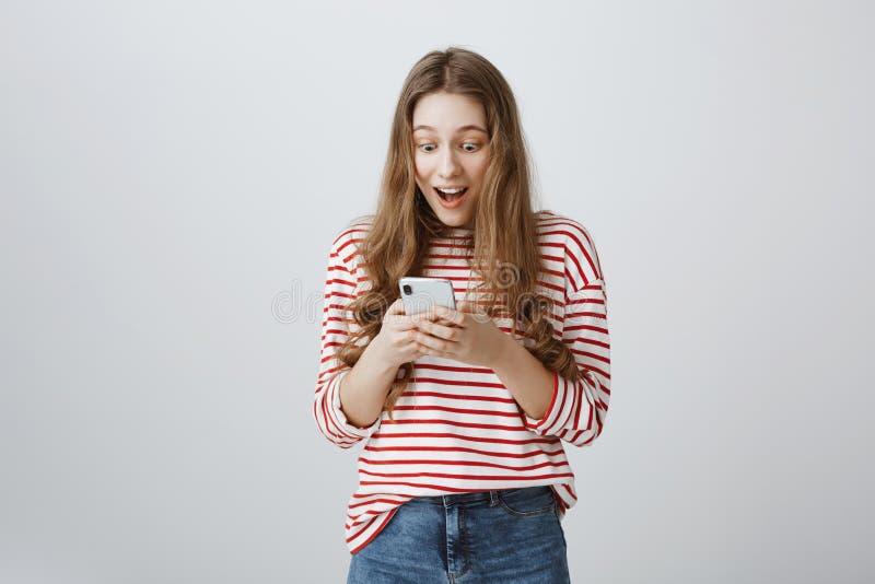 梦想实现在技术帮助下 时髦现代妇女画象有拿着智能手机的长的金发的,看 库存照片