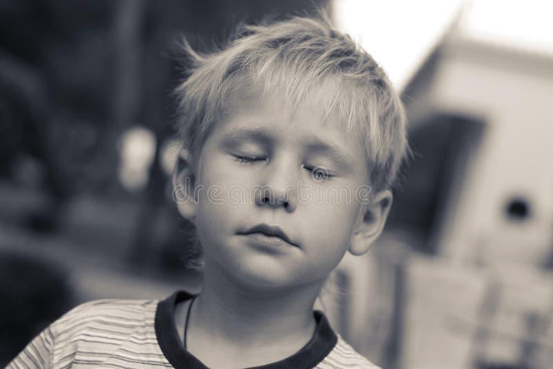 梦想家 美丽的男孩,他的注视闭合 图库摄影