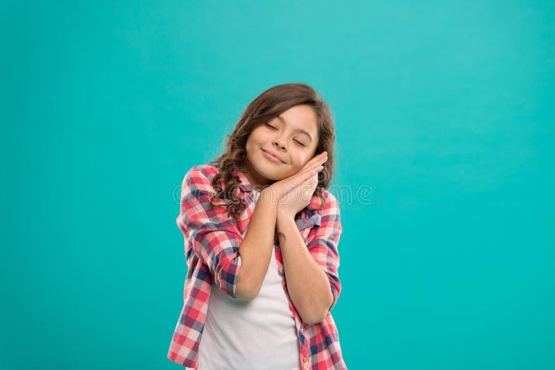 梦想甜点 孩子女孩在面颊的举行手作为睡眠姿态  晚安和有好的梦想 困平安 免版税库存照片