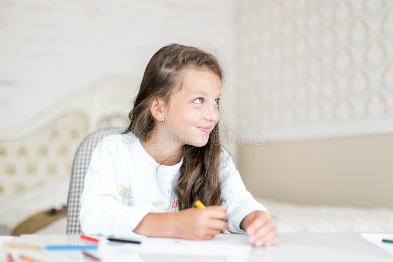 梦想的孩子女孩图画和油漆与颜色铅笔 免版税库存照片