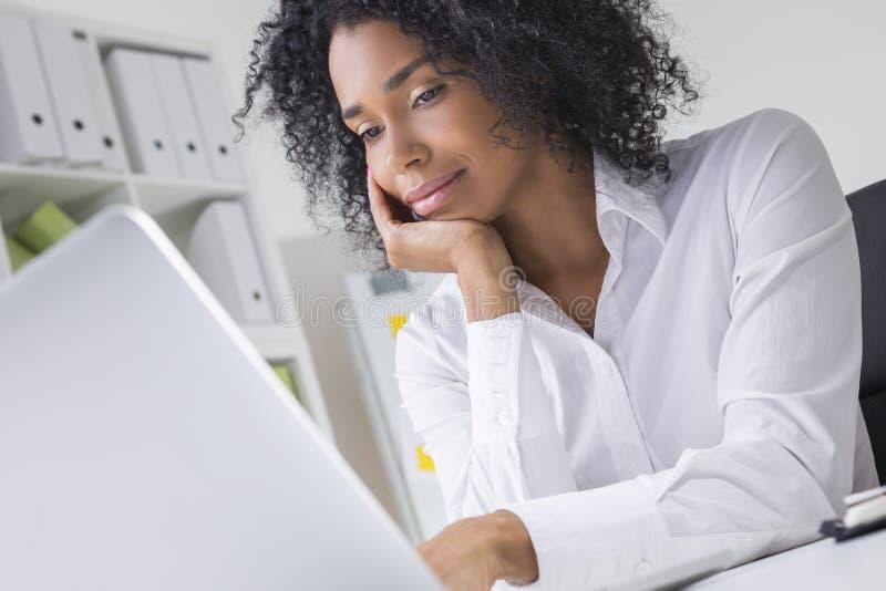 梦想的少妇在看她的膝上型计算机屏幕的空的办公室 免版税库存照片