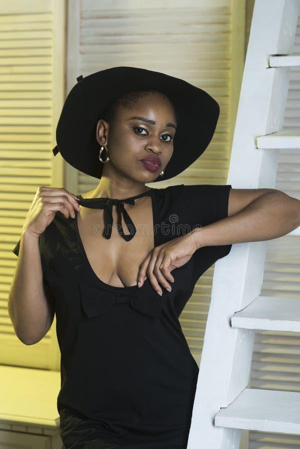梦想的面孔的夫人与构成 礼服的夫人有诱人低颈露肩的 有非洲出现的妇女在黑礼服 图库摄影
