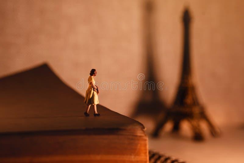 梦想目的地的假期 旅行在巴黎,法国 一名微型旅游妇女Standingon年迈的书和看 免版税库存图片
