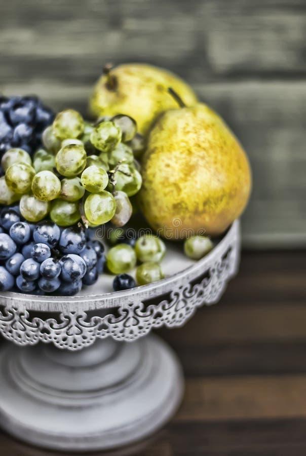 梨和葡萄在黑暗的木头 库存照片