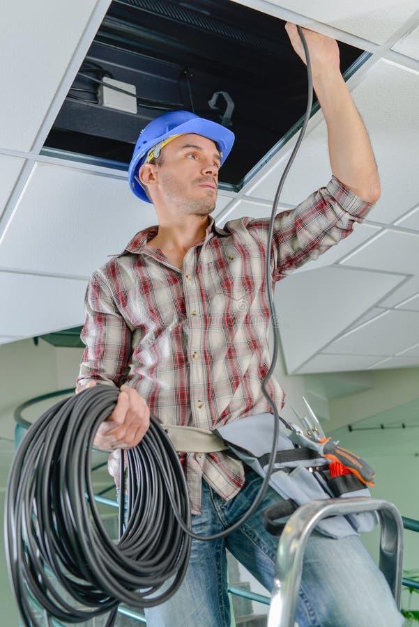 梯子的电工在自己 库存照片