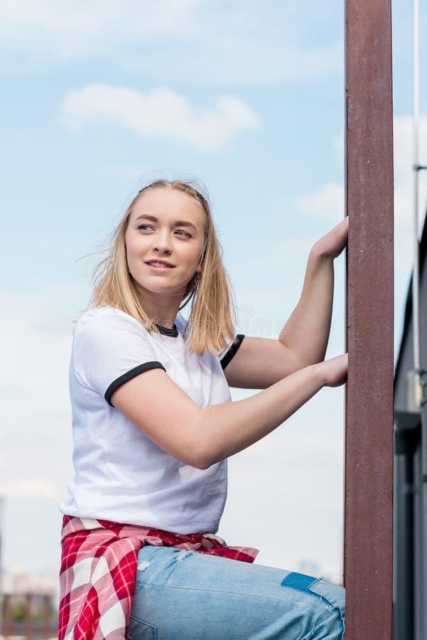 梯子的美丽的青少年的女孩在前面 库存照片