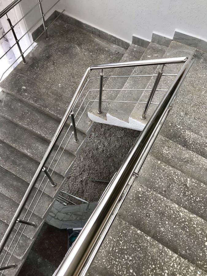 梯子行军由与不锈钢扶手栏杆的混凝土制成 白涂料和油漆污点在修理以后 免版税库存图片