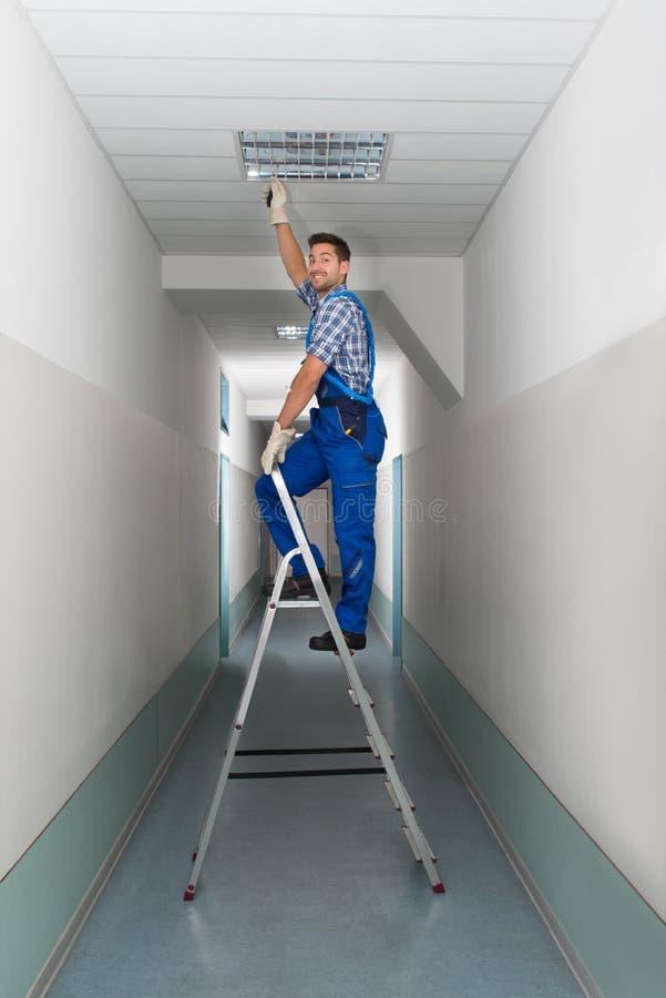 活梯的电工安装照明设备对天花板 库存照片