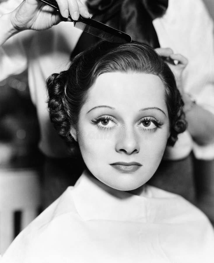 梳一根少妇的头发的美发师(所有人被描述不更长生存,并且庄园不存在 供应商保单t 库存图片