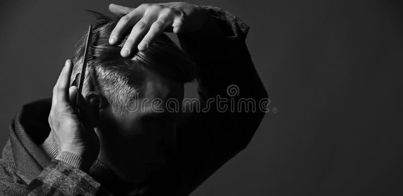 梳他的头发的葡萄酒样式的人 衣服的理发师 库存图片
