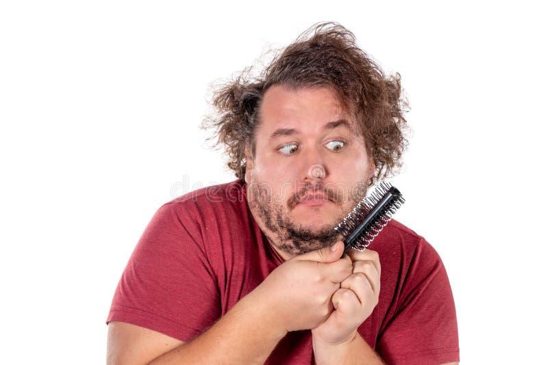 梳他的有在白色背景隔绝的一把小黑梳子的被缠结的和淘气头发的肥胖人尝试接近的画象  库存照片