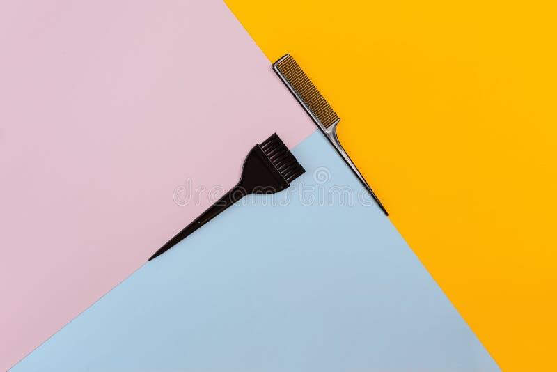 梳和在颜色桃红色的刷子,黄色,蓝纸背景 顶视图 库存照片