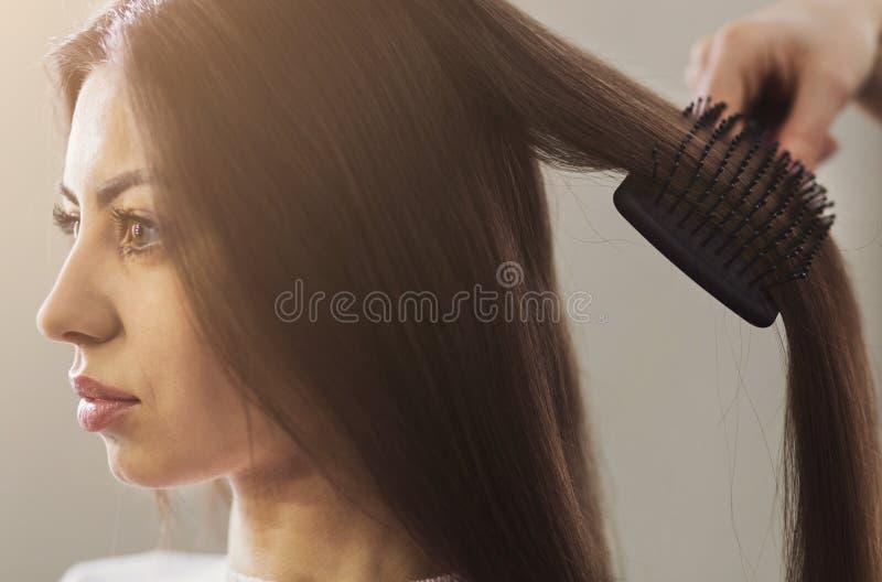 梳在一个专业沙龙的美发师妇女头发 免版税库存照片