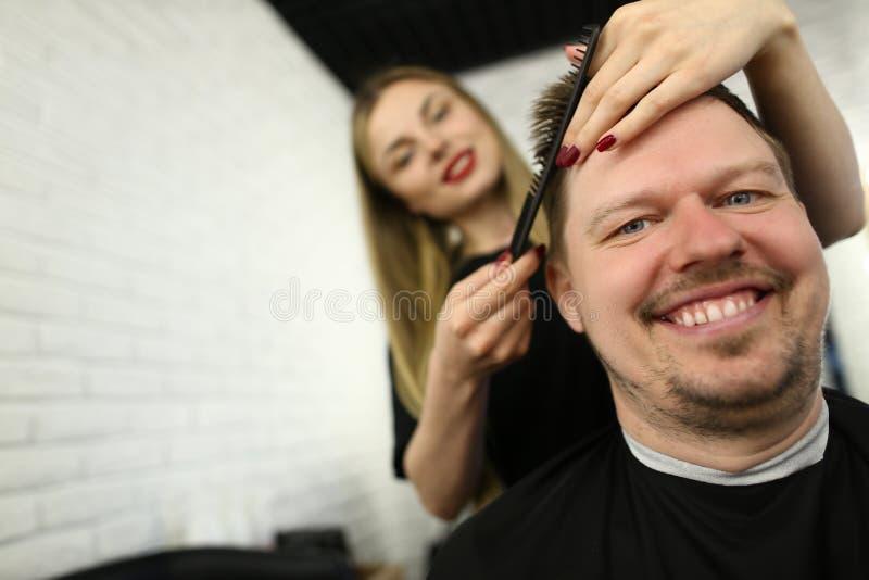 梳在发廊的美发师男性头发 免版税图库摄影