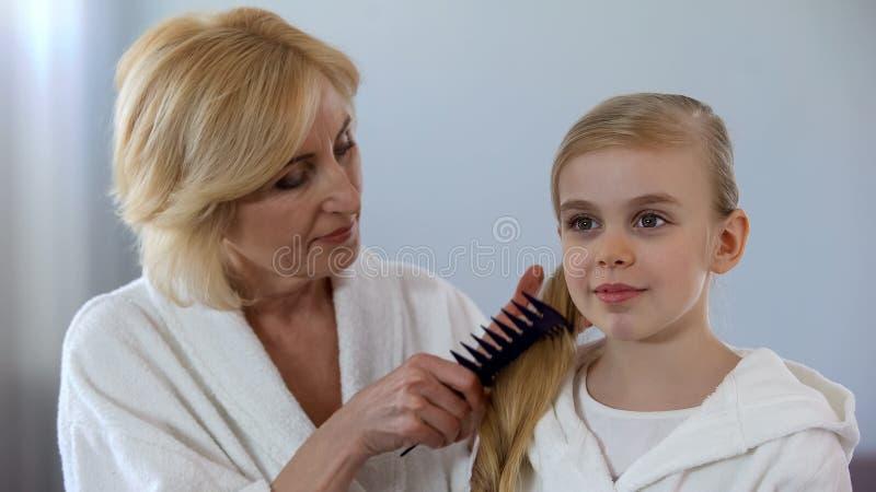 梳在镜子,家庭爱前面的有同情心的祖母孙女头发 免版税库存照片