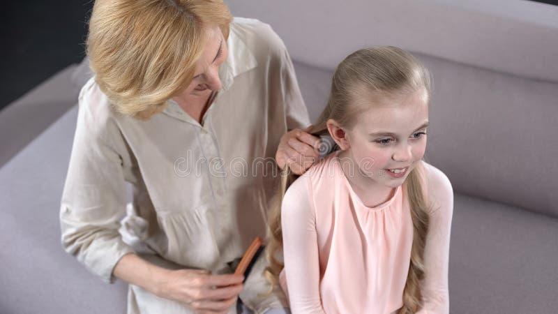 梳女孩头发的年长保姆,准备集会小学,关心 免版税图库摄影