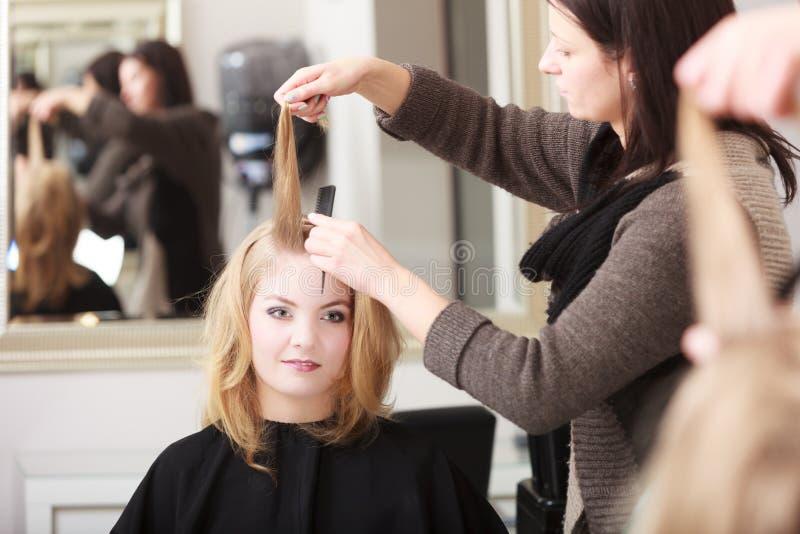 梳女性理发沙龙的发式专家客户白肤金发的女孩 图库摄影