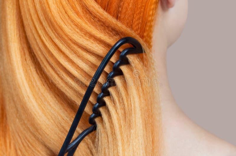 梳她他的美容院的客户的长的红色头发的美发师 免版税库存照片