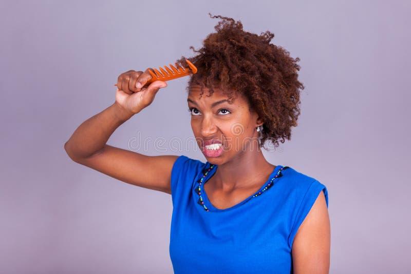 梳她卷曲的非洲的头发- Blac的年轻非裔美国人的妇女 免版税库存照片