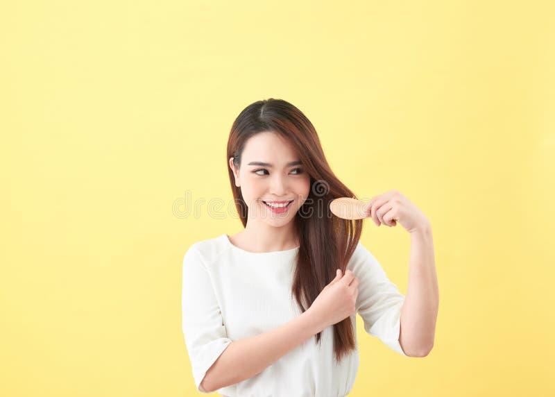 梳她头发和微笑的美丽的年轻女人画象 免版税库存图片