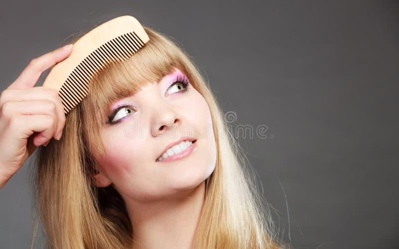 梳她的与梳子的特写镜头妇女边缘 免版税库存图片