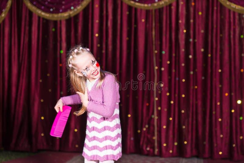 梳她的有一把巨大的桃红色梳子的滑稽的女孩头发 免版税库存图片