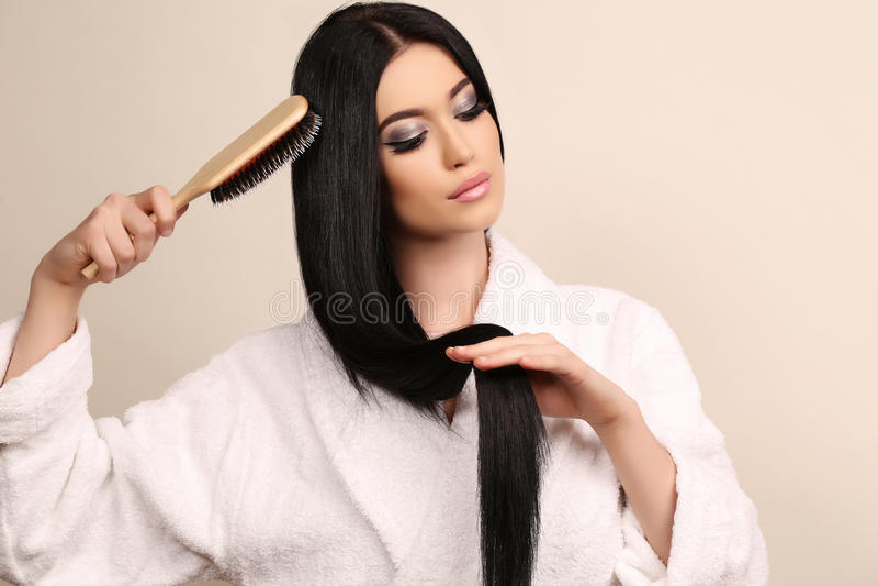 梳她的豪华健康头发的美丽的肉欲的妇女 免版税库存图片