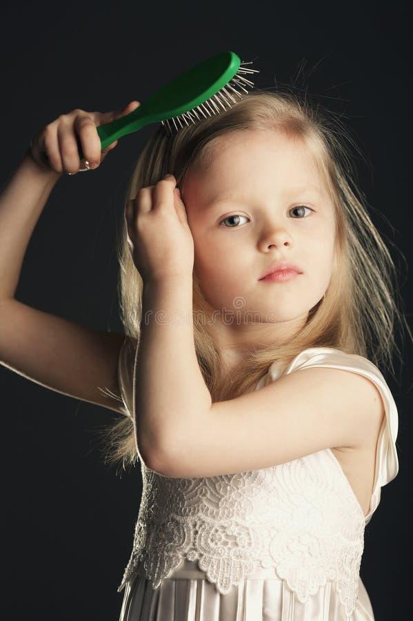 梳她长的头发的小女孩 图库摄影