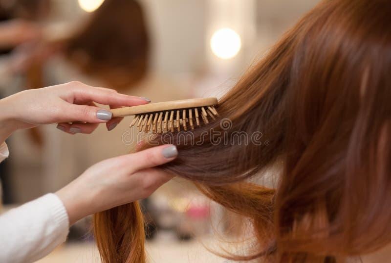 梳她他的美容院的客户的长,红色头发的美发师 免版税库存照片