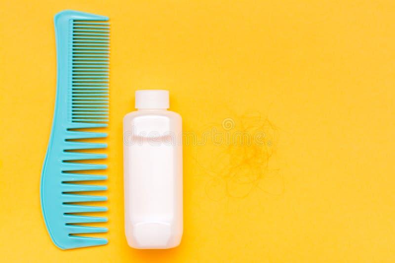 梳子、瓶有香脂的和下落的头发一束在黄色bac 免版税库存图片