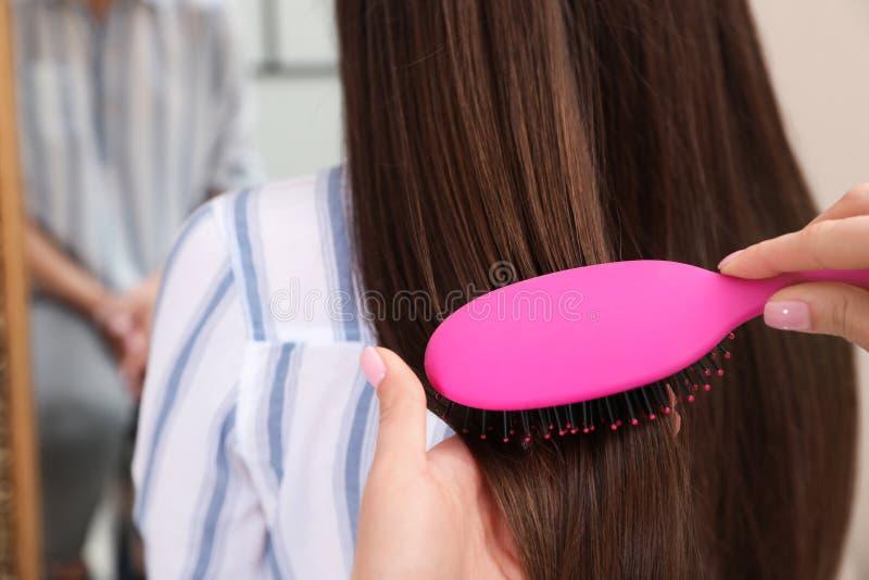 梳有坐垫刷子的妇女朋友的头发户内 库存照片