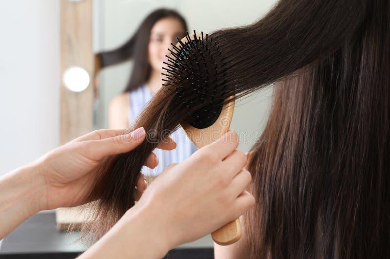 梳有坐垫刷子的妇女朋友的头发户内 免版税库存图片