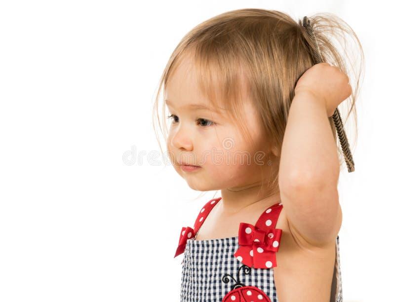 梳有老梳子的逗人喜爱的年轻白种人女孩头发 免版税图库摄影