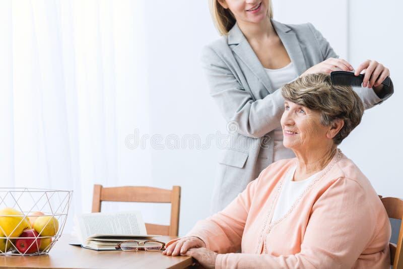梳祖母的头发的孙女 免版税图库摄影